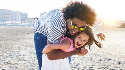 cute mixed race child playing with afro hair father on beach. concept of diversity and family fun.