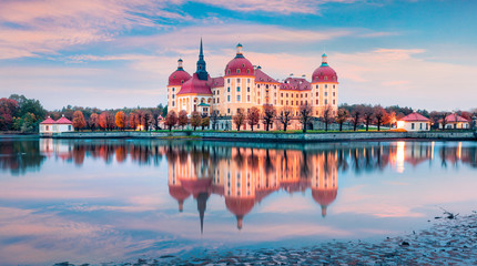 Beautiful morning panorama of Moritzburg Baroque palace surrounded by a lake. Great autumn sunrise in Saxony, Dresden location, Germany, Europe. Traveling concept background.