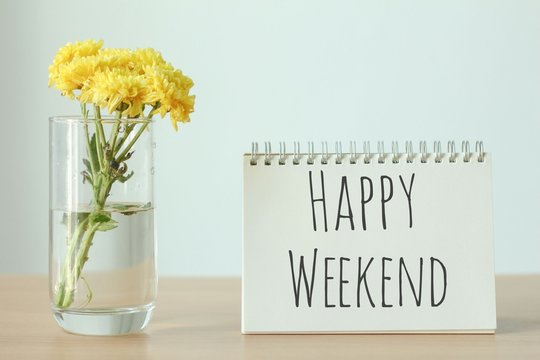 Yellow flower in glass with happy weekend notebook on wood table on white background.