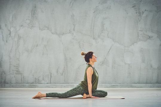 Gorgeous fit Caucasian brunette doing Half Pigeon yoga pose on mat barefoot.