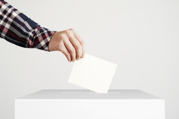 Man putting a ballot into a voting box.