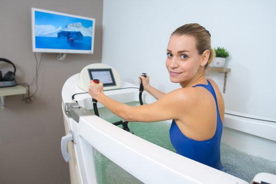woman in swimming-pool doing aquabike exercises