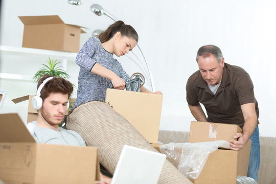 family preparing cardboard boxes idle boy on laptop
