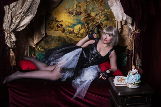 Pretty gothic girl with cards in a dark room interior