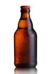 small bottle of beer with drops on a white background