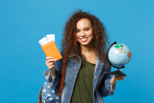 Young african american girl teen student in denim clothes, backpack hold pass isolated on blue wall background studio portrait. Education in high school university college concept. Mock up copy space.