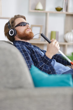 blind man on a sofa using headphones