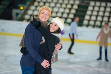 young happy loving couple skating at ice rink