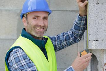 Fototapeta construction worker laying bricks and using measuring tape obraz