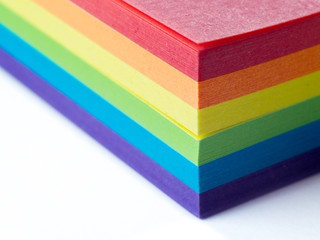 Block of sticky notes in LGBT colors isolated on a white background. Macro, shallow depth of field.