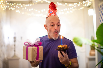 Man blows out a candle on the cake, holding a present in his hand - birthday celebration concept
