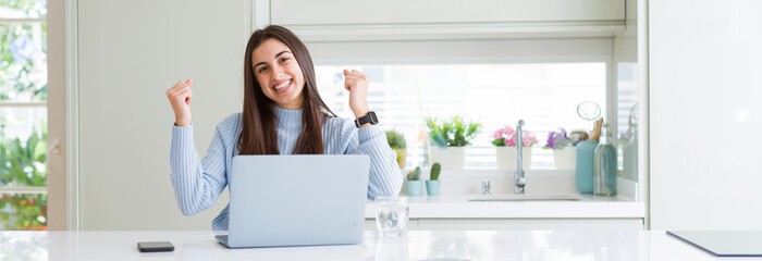 Wide angle picture of beautiful young woman working or studying using laptop screaming proud and celebrating victory and success very excited, cheering emotion