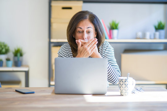 Middle age senior woman sitting at the table at home working using computer laptop shocked covering mouth with hands for mistake. Secret concept.