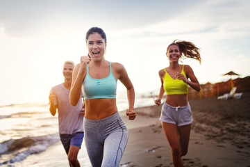 Group of young friends running and exercising on the beach