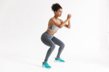 Amazing stronger sports fitness african woman make exercises isolated over white wall background.