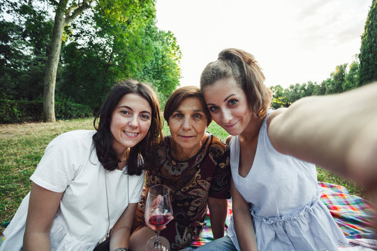 Mother and daughters take selfie embraced in a park at sunset on summer evening