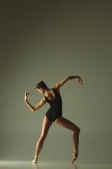 Graceful ballet dancer or classic ballerina dancing isolated on grey studio background. Showing...