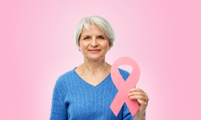 health, charity and old people concept - portrait of smiling senior woman with breast cancer awareness ribbon over pink background
