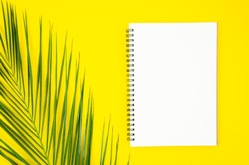 Spiral notepad with tropical palm leaf mockup on yellow background. Minimal summer concept. Frame with copy space