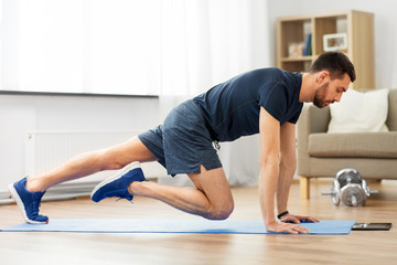 sport, fitness and healthy lifestyle concept - man with tablet computer doing running plank...