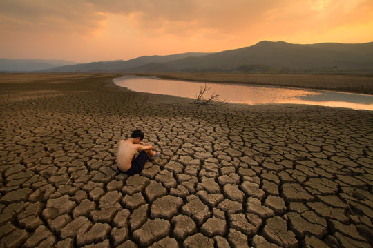 Water crisis, Sad Children sitting on cracked earth near drying water at the river metaphor climate change, Global warming, Environment pollution.
