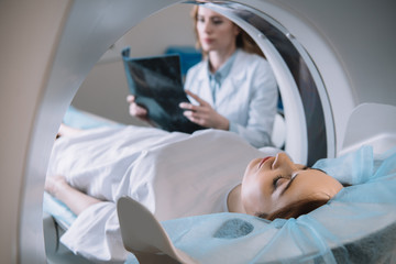 selective focus of radiologist holding x-ray diagnosis while patient lying on ct scanner bed during diagnostics Wall mural