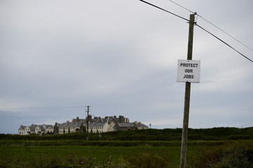 A sign reading 'Protect our jobs' is affixed to an electricity pole on the road leading to U.S. President Donald Trump's Doonbeg Golf club which is visible in the distance, ahead of his visit to Doonbeg