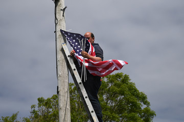 Danny Buckley places a U.S. flag on an electricity pole to festoon the streets of Doonbeg village ahead of a visit by U.S. President Donald Trump to his golf course in the County Clare village of Doonbeg