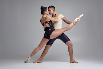 Two athletic modern ballet dancers are posing against a gray studio background.