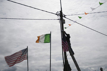 Tommy Haugh climbs a ladder to affix a U.S. flag to an electricity pole to festoon the streets of Doonbeg village with U.S. and Irish colours ahead of a visit by U.S. President Donald Trump to his golf course in the County Clare village of Doonbeg
