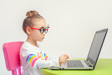 beautiful cute little girl typing on laptop computer at home
