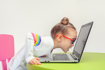 Excited beautiful little girl looking at laptop screen very closely
