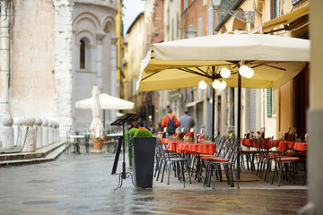 Beautifully decorated small outdoor restaurant tables in the city of Lucca, Italy Wall mural