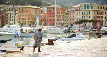 Woman walking her dog in marina of Santa Margherita Ligure town, located in Liguria, Italy