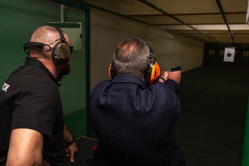 Shooting in the dash of short-barreled weapons. A man aims at a target before firing a pistol. The instructor in special ballistic headphones controls the process