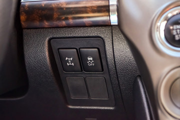 The button for the stability control system and locking the center differential on black panel of car near the steering wheel to overcome off-road, impassable roads and drive safely in snow or rain