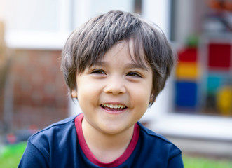 Portrait of adorable kid looking out with smiling face, Head shot mixed race child looking at camera, Photo of happy boy playing in the garden in sunny day summer, Positive kid concept