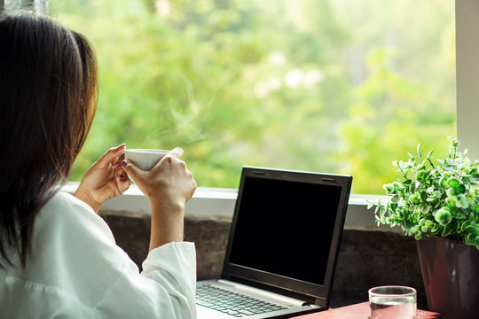 Asian business woman drinking coffee at home office enjoying the view of nature from window with laptop on desk