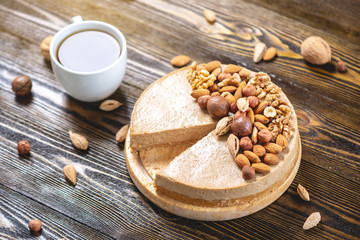 Nutty caramel cheesecake cake with topping of walnut, almond, hazelnut and macadamia on a dark wooden background.