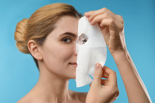 Beautiful woman with cotton facial mask sheet against color background