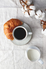 Cup of black coffee with croissant and milk on  table. The concept of breakfast, flat lay, top view.