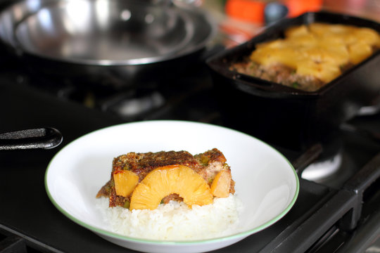Plate of Hawaiian style meatloaf with rice on the stove.