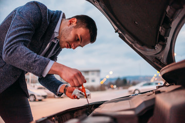Fotobehang Zeilen Young manager formally dressed checking his car oil at sunset while leaning under the car's hood.
