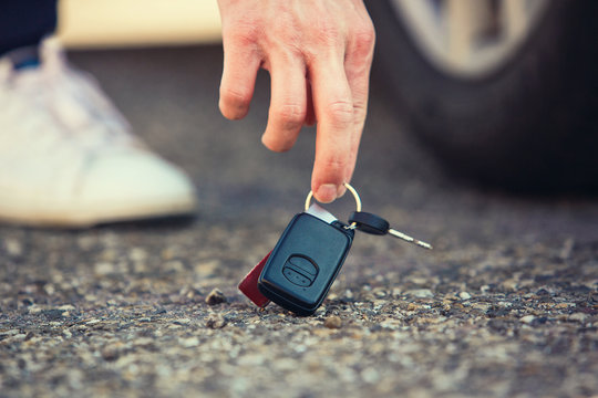 Close up of man hand lifting car keys fallen on the ground. Guy found vehicle keys someone lost on the asphalt road in the parking.