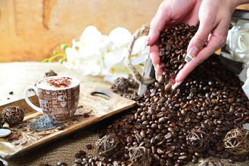 Cappuccino Hand mit fallenden Bohnen