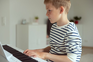 Teenager boy has training course with e-piano at home
