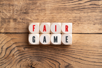 """cubes showing the message """"fair game"""" on wooden background"""