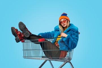 Obraz Confident weird female in shopping trolley - fototapety do salonu