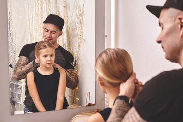 Cute little daughter and her tattoed dad are playing together near a mirror. Dad is doing his daughter's hair. Family holiday and togetherness.
