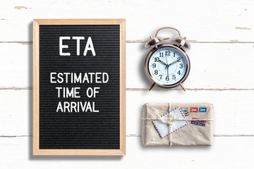 letterboard with acronym ETA and a package and a clock on wooden background